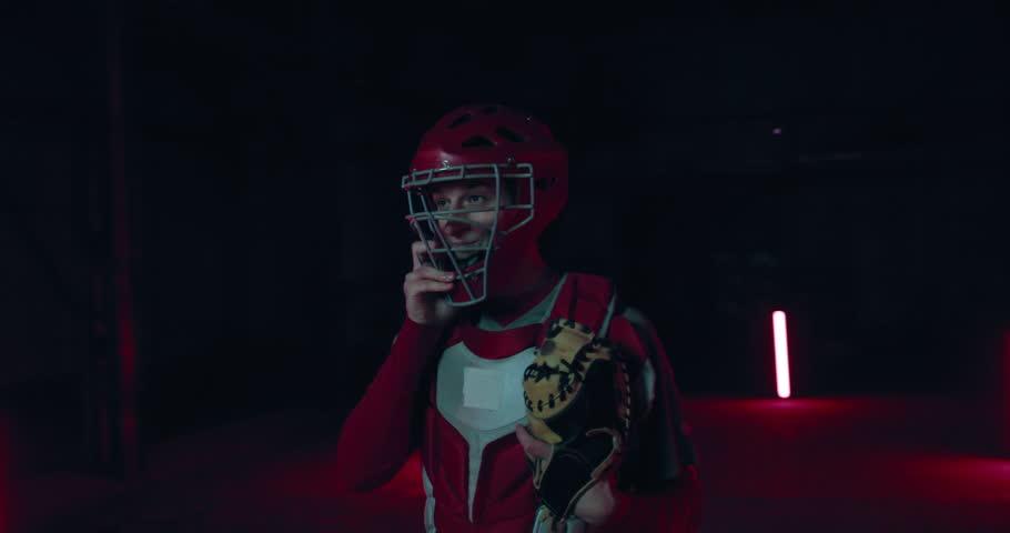 ORBITAL SHOT Caucasian professional baseball player catcher posing against dark background. 4K UHD 60 FPS SLOW MOTION #1026481460