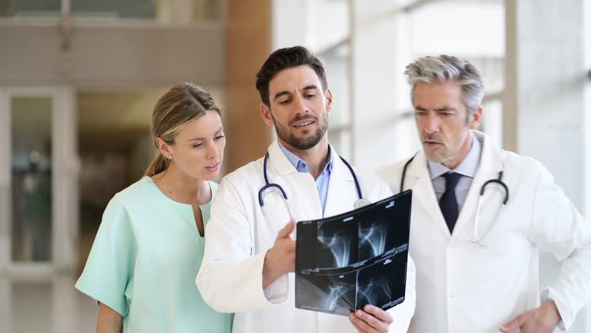 Doctors and nurse talking and walking with X-Ray in modern hospital