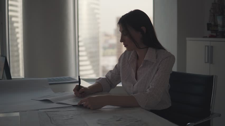 Silhouette of a business woman working late in the evening in the office. girl works with documents while sitting at the table | Shutterstock HD Video #1026500948
