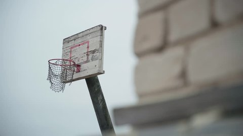 Old basketball hoop with torn net hanging in wind and peeled off paint