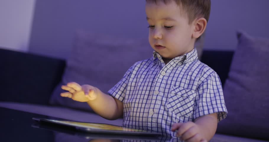 Cute Child Entertaining With Tablet. Little Boy Spending Leisure Time Playing Mobile Game in the and Crushes the Bright Screen With Her Hand. Concept of:Happy Childfood, Technology, Childen Play Games | Shutterstock HD Video #1026524723