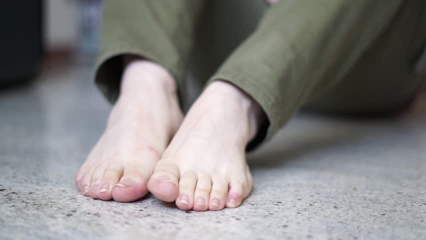 Young woman walking. Nude female feet close up against marble floor #1026525620