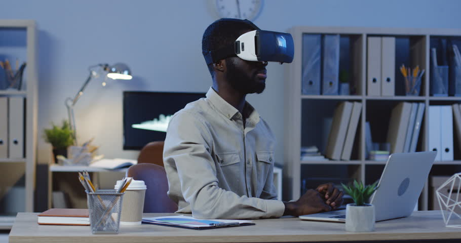 Young African American male office manager sitting late in the evening in hi office, having a VR headset, scrolling and taping in the air.
