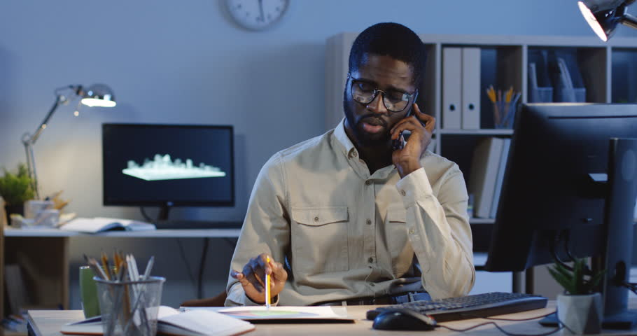 Young handsome worried African American businessman having a late night call while working in his office room, speaking and consulting about some documents of project.