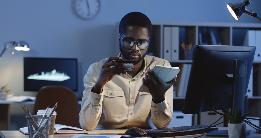 African American young good looking man in glasses paying with a credit card while buying online on the tablet device in the office late in the evening.