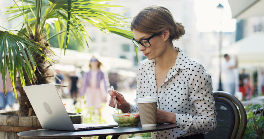 Portrait shot of the good looking businesswoman in the glasses having a lunch in the restaurant terrace while sitting at the laptop computer. Outside. | Shutterstock HD Video #1026527264