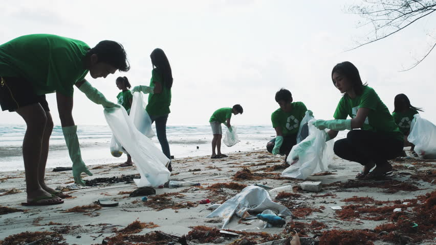 Asian group volunteer member cleaning summer beach and keeping garbage together in cleaning day. Concept of waste environment, recycle, ecology, pollution and volunteer. 4k resolution. | Shutterstock HD Video #1026546056