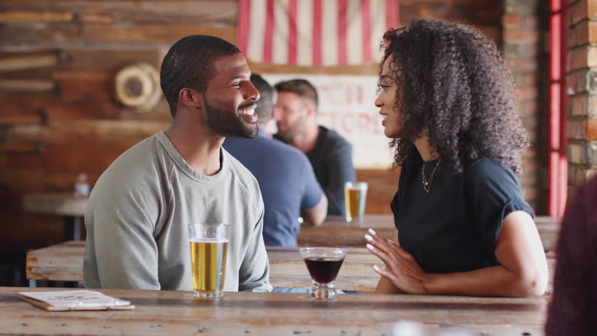 Young Couple Meeting In Sports Bar Enjoying Drink Before Game #1026549719