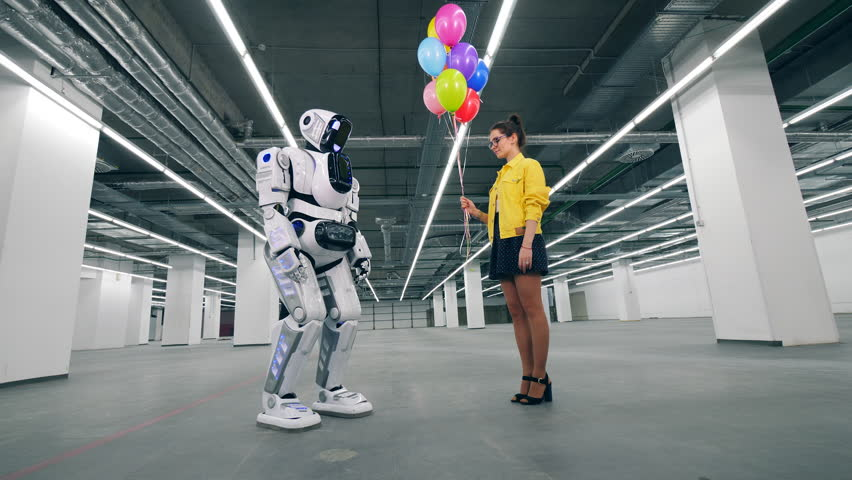 Human-like robot and a girl are holding balloons together | Shutterstock HD Video #1026557546