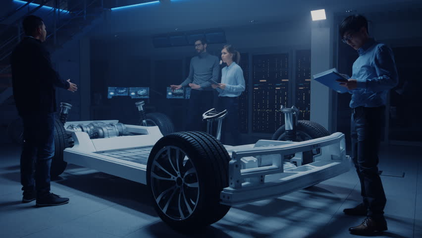 Team of Automobile Design Engineers Enter Automotive Innovation Facility Start Working on Electric Car Platform Chassis that Includes: Tires, Suspension, Engine and Battery #1026560735