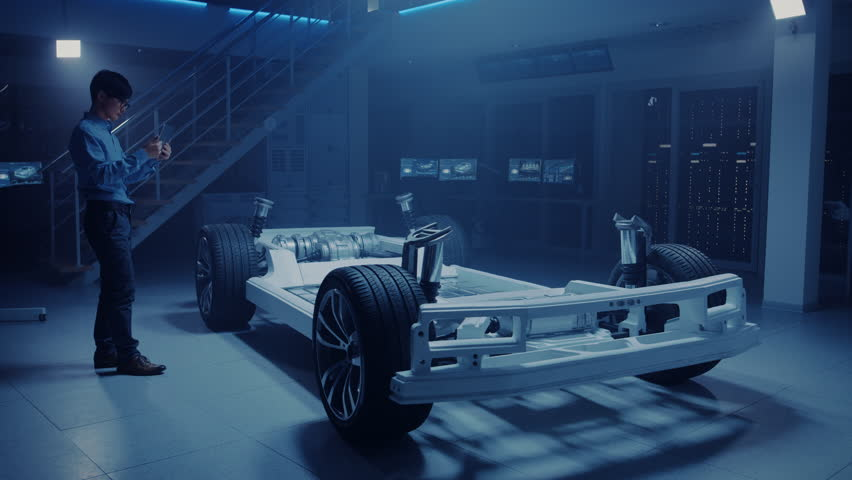 Automobile Engineer Working on Electric Car Chassis Platform, Using Tablet Computer Augmented Reality with 3D CAD Software Modelling. Innovative Facility: Vehicle Frame with Wheels, Engine, Battery | Shutterstock HD Video #1026560948