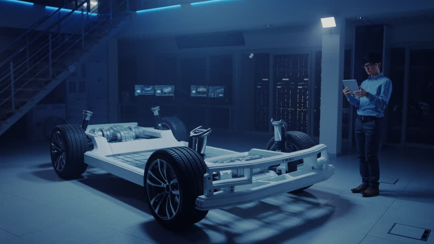 Automobile Engineer Working on Electric Car Chassis Platform, Using Tablet Computer Augmented Reality with 3D CAD Software Modelling. Innovative Facility: Vehicle Frame with Wheels, Engine, Battery | Shutterstock HD Video #1026560954
