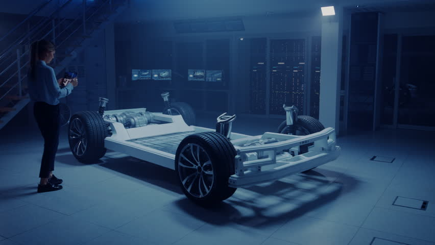 Automobile Engineer Working on Electric Car Chassis Platform, Using Tablet Computer Augmented Reality with 3D CAD Software Modelling. Innovative Facility: Vehicle Frame with Wheels, Engine, Battery #1026560957