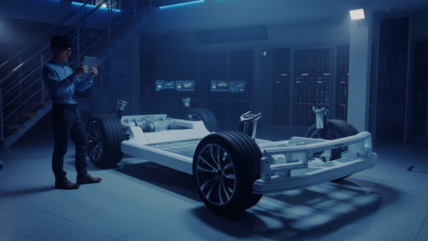 Automobile Engineer Working on Electric Car Chassis Platform, Using Tablet Computer Augmented Reality with 3D CAD Software Modelling. Innovative Facility: Vehicle Frame with Wheels, Engine, Battery #1026560969
