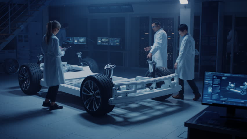 Team of Automotive Engineers and Scientists Discussing, Designing and Working on Electric Car Platform Chassis Prototype. Using 3D CAD Software, Analysing Efficiency. Shot on 8K RED Camera.