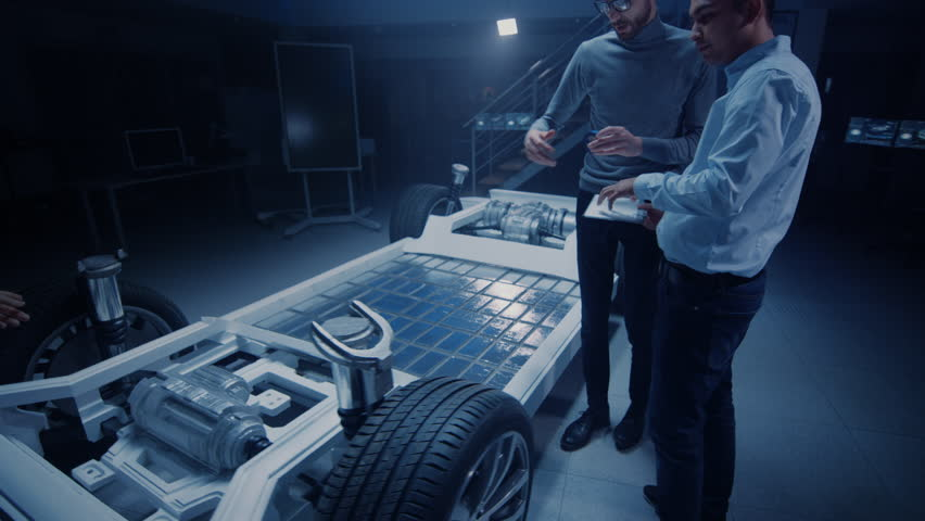 Team of Automotive Engineers Working on Electric Car Platform Chassis Prototype, Taking Measures, working with 3D CAD Software, Analysing Efficiency. Shot on 8K RED Camera