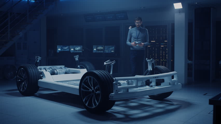 Automobile Engineer Working on Electric Car Platform Chassis Prototype, Using Tablet Computer with 3D CAD Software Modelling. Innovative Facility: Vehicle Frame with Wheels, Engine,Battery. Shot on 8K #1026561170