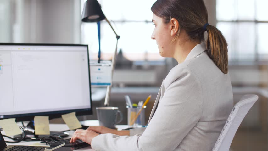 business, programming and technology concept - female programmer with computer working and taking folder from her colleague at office #1026569966