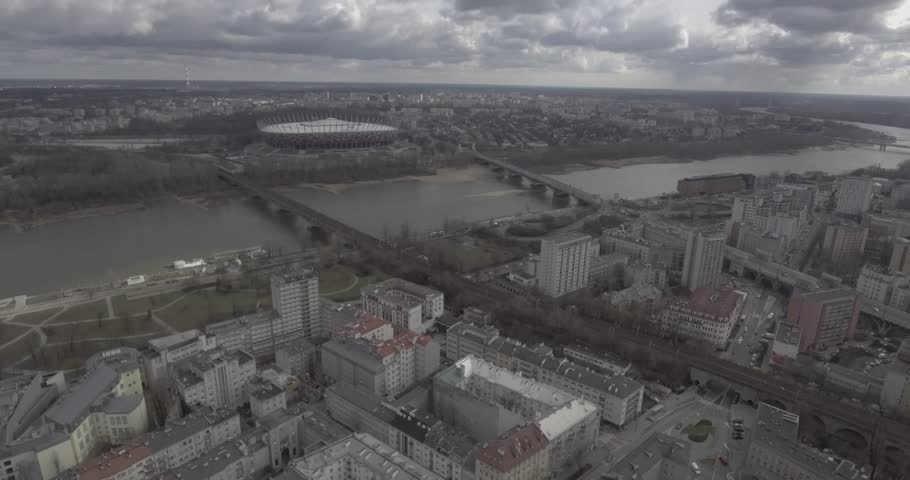 4K. Aerial view of high-speed trains passing through the center of Warsaw. Trains passing through the yellow buildings by the river Vistula. Taken from the drone in RAW  format. | Shutterstock HD Video #1026570680