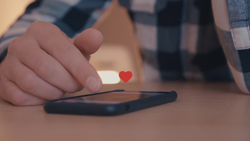 Close up of young man using smartphone with likes and loves icon floating out of smart phone | Shutterstock HD Video #1026571253