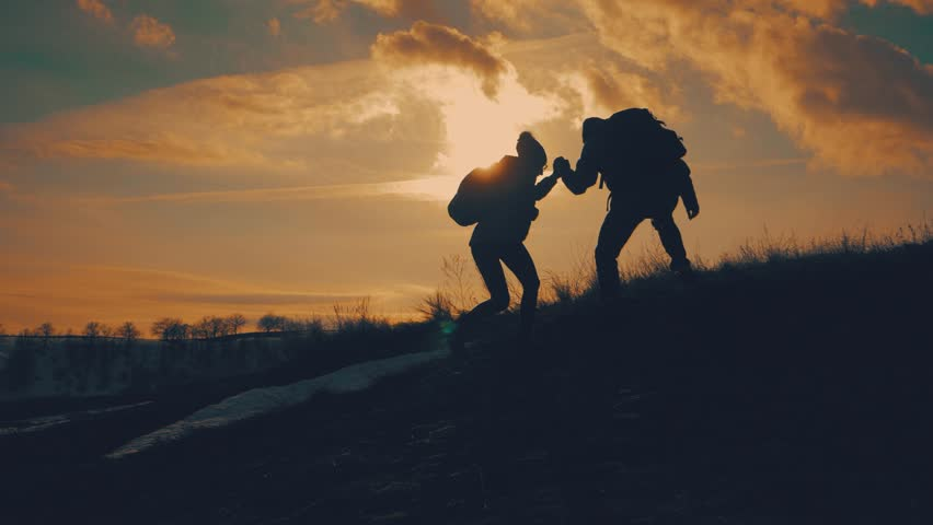 Couple hiking help each other silhouette in mountains. Teamwork couple hiking, help each other, trust assistance, sunset. Man giving hand a woman to help her to climb the mountain.