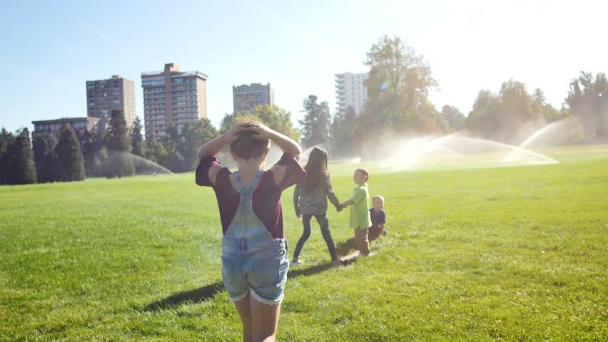 Kids playing tag in a city park full of sprinklers | Shutterstock HD Video #1026611066