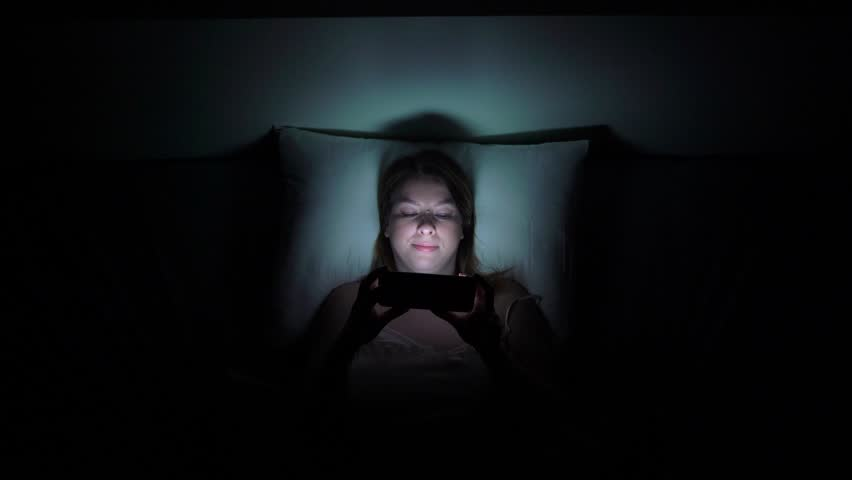 Young woman using mobile phone on the bed before she sleeping at night. Mobile addict or insomnia concept. | Shutterstock HD Video #1026618863