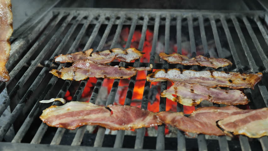 Slices of bacon are grilled, the fat from the bacon is drained from the fried bacon, the chef in black gloves with iron tongs turns over the slices of bacon alternately for the final preparation   Shutterstock HD Video #1026630566
