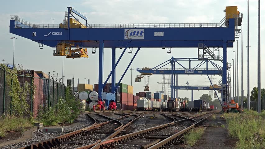 DUISBURG / GERMANY - MARCH 2019 : Gantry crane is unloading and loading container from a train at daytime in the port of Duisburg - Germany