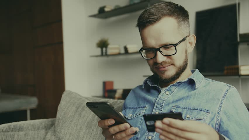 Young european man sitting on the couch, using smart phone for online shopping with credit card on living backround. Indoor.   Shutterstock HD Video #1026634037