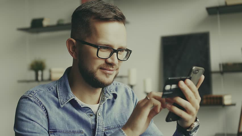 Young european man sitting on the couch, using smart phone for online shopping with credit card on living backround. Indoor.   Shutterstock HD Video #1026634040