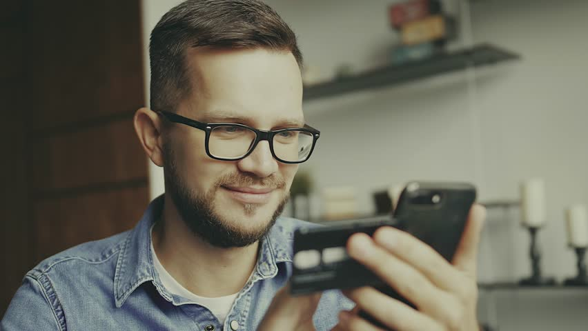 Young european man sitting on the couch, using smart phone for online shopping with credit card on living backround. Indoor.   Shutterstock HD Video #1026634043