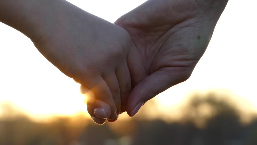 Close the hands of mother and child. Hold hands at sunset. Give a hand to a friend. The sun's rays shine through their fingers. Love, Happiness and Friendship. Hands close up.