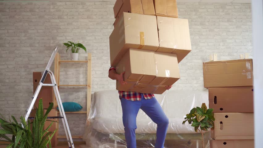 Man with large boxes in his hands falls on the sofa   Shutterstock HD Video #1026672125