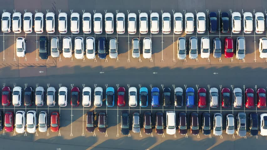 Aerial top view of the dealership parking lot with a rows of new cars on a sunny day | Shutterstock HD Video #1026673259