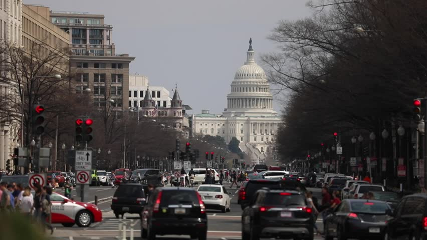 Washington, D.C. / USA - March 30, 2019: Cars and pedestrians create commuter traffic on a busy spring day on Pennsylvania Avenue with a view of the US Capitol building in the distance.