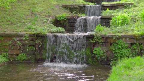 beautiful stepped waterfall, spring clear water flows through stones stairs among green grass and plants in nature in Slow motion