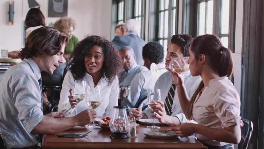 Business Colleagues Sitting Around Restaurant Table Enjoying Meal Together #1026690455