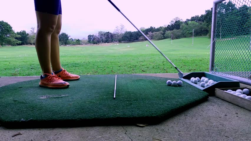 Young Woman Practicing On A Golf Driving Range With An Iron