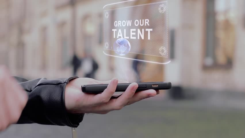 Male hands show on smartphone conceptual HUD hologram Grow our talent. Man with the future technology mobile holographic screen on blurred background of the university | Shutterstock HD Video #1026711494