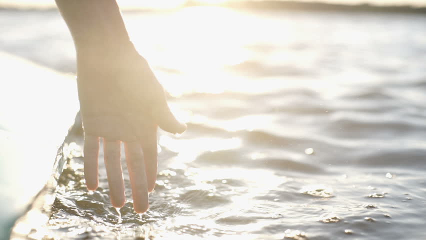 At sunset, close-up the hand of a girl moving through the water #1026715013