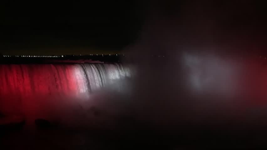 Footage video of illuminated glowing red and white Niagara Falls at night, filmed  from Canadian side. Horseshoe Falls, Canada, Ontario.