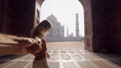 Follow me to the Taj Mahal, India. Female tourist leading way to boyfriend to magnificent famous Mausoleum in Agra. People travel concept - Girl holding man hand at sunrise traveling together- Slow mo