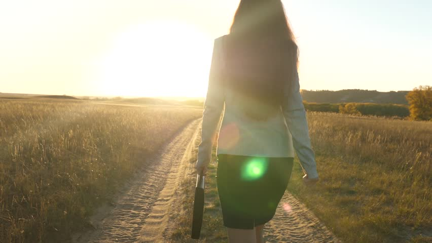 Sexy business woman girl working in rural area. woman farmer inspects land at sunset. agricultural business concept. business woman walking along a country road with briefcase in her hand. | Shutterstock HD Video #1026744158