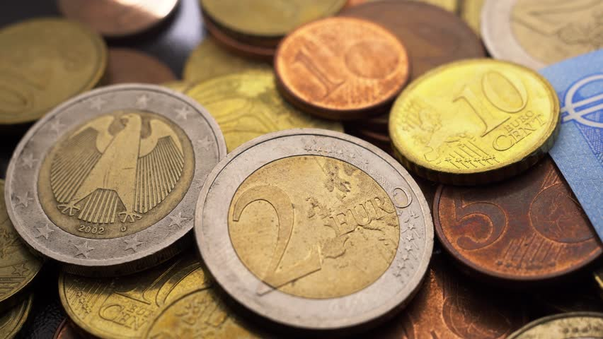 Slow pan to the right of a bunch of euro coins and bills in a close view. | Shutterstock HD Video #1026753281