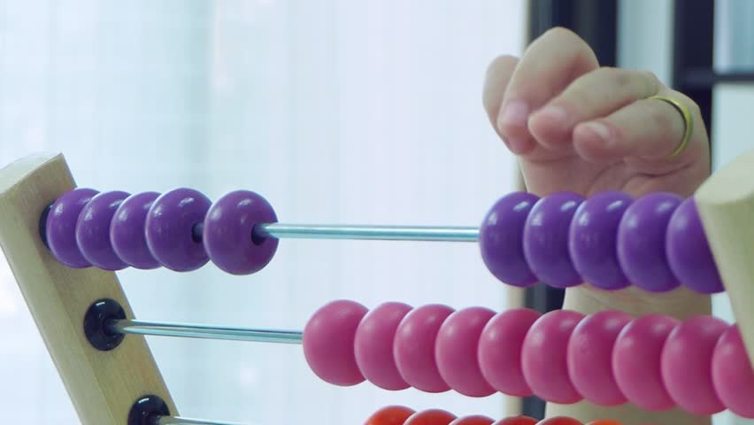 Hand of a girl playing with colorful wooden abacus
