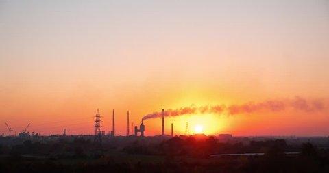 Plant, smoke pipes, sunset