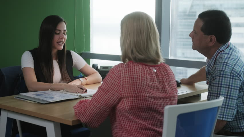 Woman at work as advisor with old couple or financial consultant talking to elderly people. Senior husband and wife meeting health insurance broker or retirement plan agent expert in bank and finance