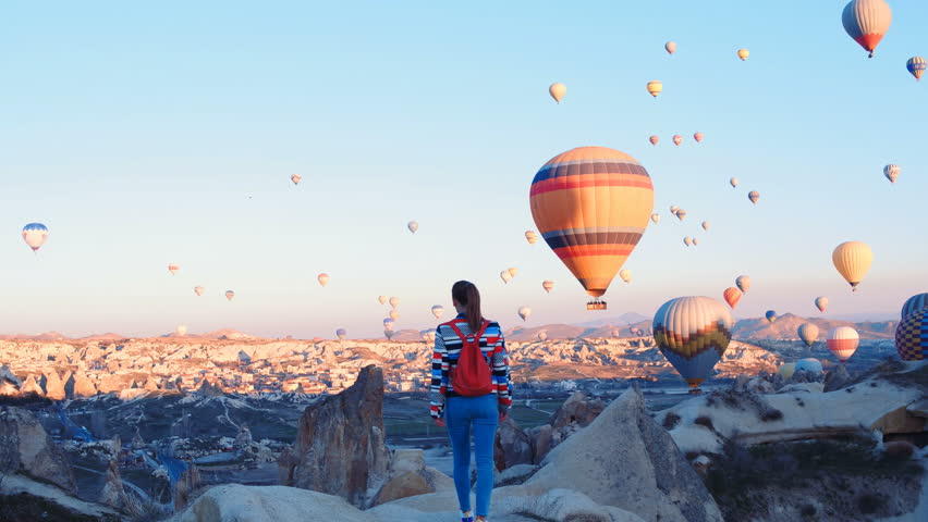 Yoing traveler with backpack looking to the air baloons. sporty girl and a lot of hot air balloons. The feeling of complete freedom, achievement, achievement, happiness Royalty-Free Stock Footage #1026792233