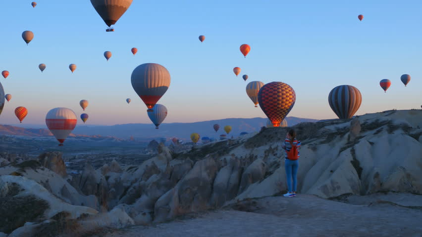 Yoing traveler with backpack looking to the air baloons. sporty girl and a lot of hot air balloons. The feeling of complete freedom, achievement, achievement, happiness | Shutterstock HD Video #1026792236